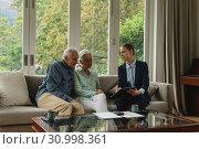 Купить «Active senior couple discussing with real estate agent over documents in living room», фото № 30998361, снято 12 марта 2019 г. (c) Wavebreak Media / Фотобанк Лори