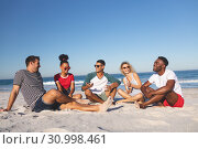 Group of friends interacting with each other on the beach. Стоковое фото, агентство Wavebreak Media / Фотобанк Лори
