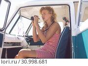 Купить «Woman taking photo with digital camera in camper van at beach», фото № 30998681, снято 15 марта 2019 г. (c) Wavebreak Media / Фотобанк Лори