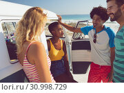 Купить «Group of friends talking with each other near camper van at beach in the sunshine», фото № 30998729, снято 15 марта 2019 г. (c) Wavebreak Media / Фотобанк Лори