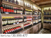 Купить «Georgian bottled wines on shelves and racks in a shop of Kindzmarauli Corporation plant», фото № 30999477, снято 1 октября 2018 г. (c) Юлия Бабкина / Фотобанк Лори