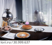 Russian table with samovar, pancakes, sour cream and hot tea. Siberian cat sitting behind a curtain and looking at the table. Стоковое фото, фотограф Ирина Кожемякина / Фотобанк Лори