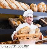 Купить «Male baker is showing tasty bread», фото № 31000081, снято 22 апреля 2017 г. (c) Яков Филимонов / Фотобанк Лори