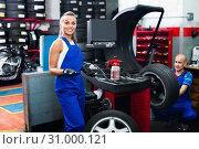 Купить «Mechanic woman working on new tire fitting in service point», фото № 31000121, снято 19 сентября 2019 г. (c) Яков Филимонов / Фотобанк Лори