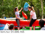 Купить «Cheerful girlfriends fighting with inflatable pillows in an amusement park», фото № 31000165, снято 20 июля 2019 г. (c) Яков Филимонов / Фотобанк Лори