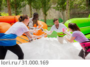 Купить «Happy friends are playing a game - who will find balls in soap suds faster», фото № 31000169, снято 22 июля 2019 г. (c) Яков Филимонов / Фотобанк Лори