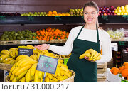 Купить «Young female in apron selling fresh bananas on the market», фото № 31000217, снято 31 января 2019 г. (c) Яков Филимонов / Фотобанк Лори