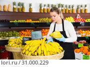 Купить «Young female seller in gloves selling fresh bananas on the market», фото № 31000229, снято 31 января 2019 г. (c) Яков Филимонов / Фотобанк Лори