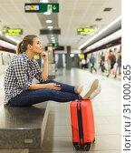 Купить «Girl sitting with legs on suitcase at metro station», фото № 31000265, снято 27 апреля 2018 г. (c) Яков Филимонов / Фотобанк Лори