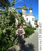 Middle-aged woman next to a bush of blooming jasmine on the background of an Orthodox church. Стоковое фото, фотограф Дмитрий Морозов / Фотобанк Лори