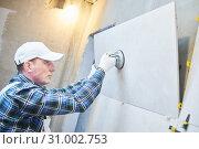 Купить «Tiler installing large format tile on wall. home indoors renovation», фото № 31002753, снято 1 апреля 2019 г. (c) Дмитрий Калиновский / Фотобанк Лори