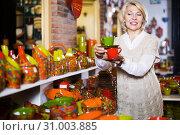 Купить «Mature female holding ceramic cups at workshop», фото № 31003885, снято 31 октября 2016 г. (c) Яков Филимонов / Фотобанк Лори