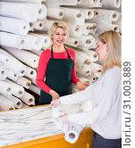 Купить «Woman seller is showing fabrics to young buyer», фото № 31003889, снято 15 февраля 2017 г. (c) Яков Филимонов / Фотобанк Лори