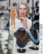 Купить «Adult woman chooses jewelry from turquoise and amber jewelery in the store», фото № 31003989, снято 2 мая 2019 г. (c) Яков Филимонов / Фотобанк Лори
