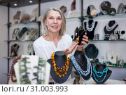 Купить «Woman trying on a aventurine necklace and earrings at a jewelry store», фото № 31003993, снято 2 мая 2019 г. (c) Яков Филимонов / Фотобанк Лори
