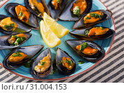 Купить «Baked mussels with lemon slices on color plate», фото № 31004153, снято 25 июня 2018 г. (c) Яков Филимонов / Фотобанк Лори