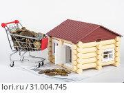 Тележка с деньгами на счетах за квартиру, рядом игрушечный домик. Стоковое фото, фотограф Иванов Алексей / Фотобанк Лори