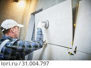 Купить «Tiler installing large format tile on wall. home indoors renovation», фото № 31004797, снято 1 апреля 2019 г. (c) Дмитрий Калиновский / Фотобанк Лори