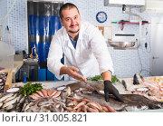 Купить «Seller shows hands fish on counter», фото № 31005821, снято 27 октября 2016 г. (c) Яков Филимонов / Фотобанк Лори