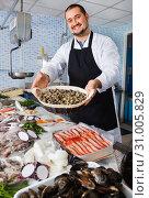 Купить «Seller holds basket of small mussels standing near a counter», фото № 31005829, снято 27 октября 2016 г. (c) Яков Филимонов / Фотобанк Лори