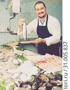 Купить «Man behind counter holding fish», фото № 31005837, снято 27 октября 2016 г. (c) Яков Филимонов / Фотобанк Лори