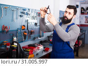 Купить «Man holds a service inspection of motorcycle parts», фото № 31005997, снято 20 июля 2019 г. (c) Яков Филимонов / Фотобанк Лори