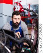 Купить «Worker repairing motorbike», фото № 31006005, снято 19 августа 2019 г. (c) Яков Филимонов / Фотобанк Лори