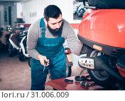 Купить «Worker inspects the motorcycle for damage», фото № 31006009, снято 8 декабря 2019 г. (c) Яков Филимонов / Фотобанк Лори