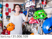 Купить «Woman choosing helmet in store», фото № 31006109, снято 24 февраля 2017 г. (c) Яков Филимонов / Фотобанк Лори