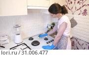 Woman cleaning the gas stove. Стоковое видео, видеограф Илья Шаматура / Фотобанк Лори