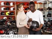 Купить «Man and woman looking for helmets», фото № 31010377, снято 16 января 2019 г. (c) Яков Филимонов / Фотобанк Лори