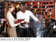 Купить «Polite smiling female seller communicating with male customer in modern motorcycle salon», фото № 31010397, снято 16 января 2019 г. (c) Яков Филимонов / Фотобанк Лори