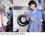 Купить «Female laundry worker sorting dirty clothes», фото № 31010593, снято 15 января 2019 г. (c) Яков Филимонов / Фотобанк Лори