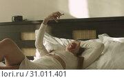 Купить «Blonde lying on bed and taking selfie in hotel room», видеоролик № 31011401, снято 5 августа 2020 г. (c) Denis Mishchenko / Фотобанк Лори