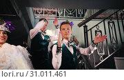 Купить «Theme party - Young people in stylish glistening retro clothes standing on the stairs and showing off their costumes», видеоролик № 31011461, снято 23 июля 2019 г. (c) Константин Шишкин / Фотобанк Лори