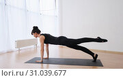 Side view of woman stands in plank with the leg raising pilates slow motion. Стоковое видео, видеограф Denis Mishchenko / Фотобанк Лори