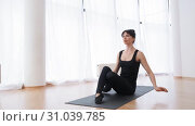 Front view of brunette caucasian woman stretching her hips anf raising legs up pilates slow motion. Стоковое видео, видеограф Denis Mishchenko / Фотобанк Лори
