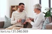 Купить «adult son and senior mother drink coffee at home», видеоролик № 31040069, снято 25 июня 2019 г. (c) Syda Productions / Фотобанк Лори