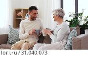 Купить «adult son and senior mother drink coffee at home», видеоролик № 31040073, снято 25 июня 2019 г. (c) Syda Productions / Фотобанк Лори