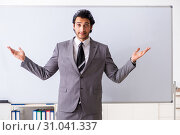 Купить «Young handsome businessman in front of whiteboard», фото № 31041337, снято 10 октября 2018 г. (c) Elnur / Фотобанк Лори