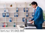 Купить «Young employee making copies at copying machine», фото № 31043985, снято 14 декабря 2018 г. (c) Elnur / Фотобанк Лори