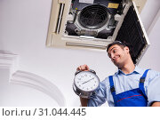 Купить «Young repairman repairing ceiling air conditioning unit», фото № 31044445, снято 27 февраля 2019 г. (c) Elnur / Фотобанк Лори