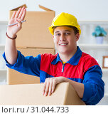 Купить «Young man working in relocation services with boxes», фото № 31044733, снято 30 июня 2017 г. (c) Elnur / Фотобанк Лори