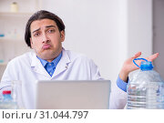 Купить «Young male chemist experimenting in lab», фото № 31044797, снято 5 марта 2019 г. (c) Elnur / Фотобанк Лори