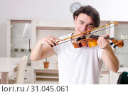 Купить «Young musician man practicing playing violin at home», фото № 31045061, снято 17 января 2019 г. (c) Elnur / Фотобанк Лори