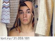 Купить «A young man with bra on his head is hiding in the closet», фото № 31059181, снято 5 августа 2017 г. (c) easy Fotostock / Фотобанк Лори
