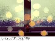 Купить «Frosted window in dark evening light, with a candle burning on a windowsill.», фото № 31072109, снято 7 июля 2014 г. (c) easy Fotostock / Фотобанк Лори