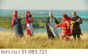 Купить «Young ensemble in traditional russian clothes dancing on the field», видеоролик № 31083721, снято 20 июля 2019 г. (c) Константин Шишкин / Фотобанк Лори