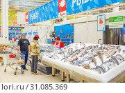 Купить «Russia Samara May 2019: a selection of fresh fish lying in the ice on the counter of a supermarket. Text in Russian: salmon, steak, piece, carp, sylvia, pollock, cod, Atlantic, smelt, herring, trout, sea bass, catfish, burbot, mackerel, bream, pike, cupid, crucian», фото № 31085369, снято 23 мая 2019 г. (c) Акиньшин Владимир / Фотобанк Лори
