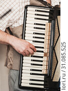 Купить «Accordionist plays accordion, vertical», фото № 31085525, снято 18 мая 2019 г. (c) EugeneSergeev / Фотобанк Лори